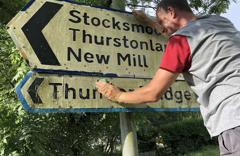 Cllr Richard Smith cleaning road signs in Kirkburton
